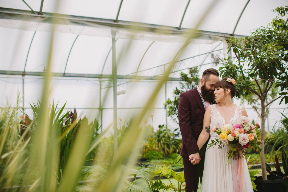 Bride and groom portrait inside the greenhouse at Secret Garden at Woodbridge Pond venue in Abbotsford